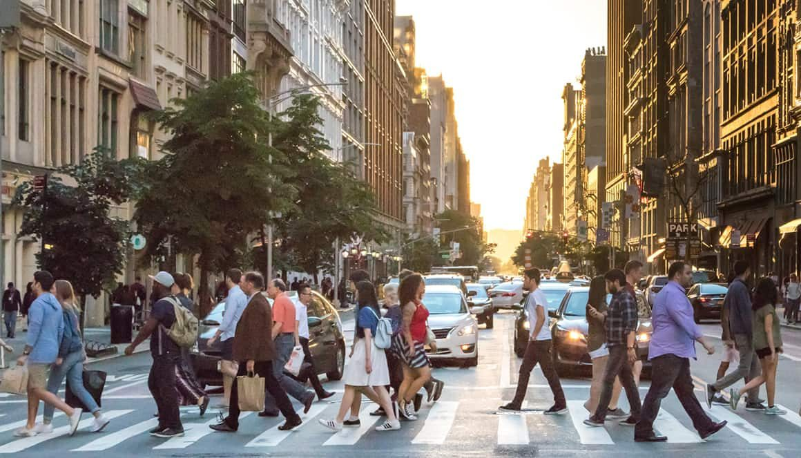 Citizens walking in their city at a pedestrian crossing.