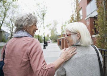 Entraide entre une travailleuse sociale et une femme âgée.