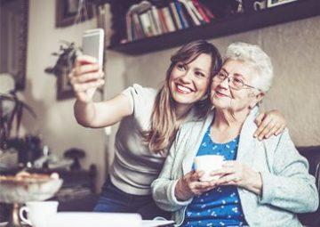 Une personne âgée et une aide à domicile prenant un selfie.