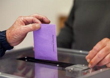 Un citoyen dépose son bulletin dans l'urne électorale.