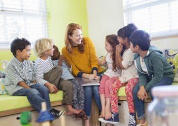Enseignante et enfants lisant dans une salle d'école.
