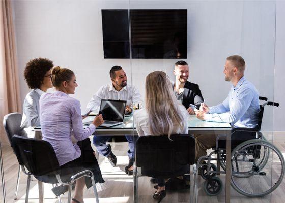 Jean, handicapé, est assis avec ses collègues en réunion.