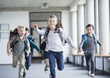 Marie et d'autres enfants courent dans le couloir de l'école.
