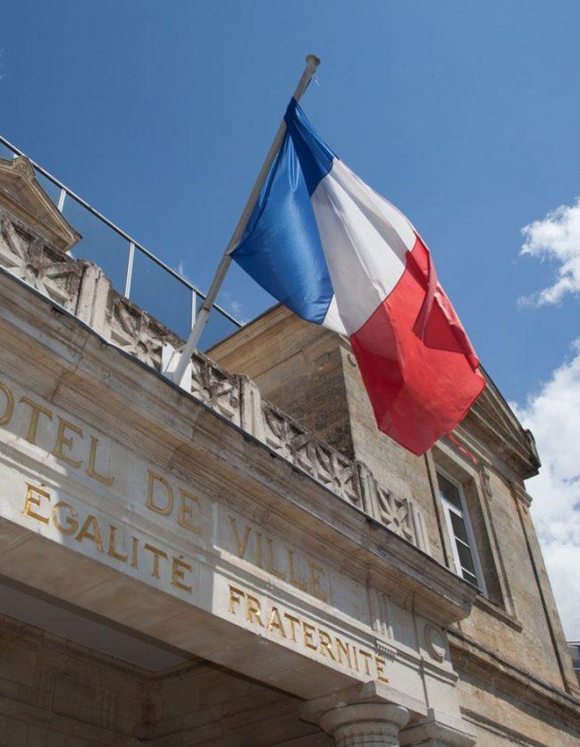 Drapeau français de pavoisement sur la façade d'une mairie.