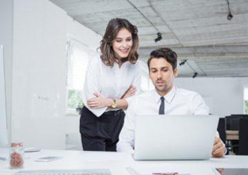 Dos analistas trabajan en el ordenador gracias a un software de gestión.