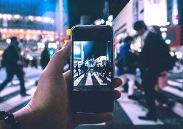 Persona fotografiando a la multitud en el paso peatonal por la noche.